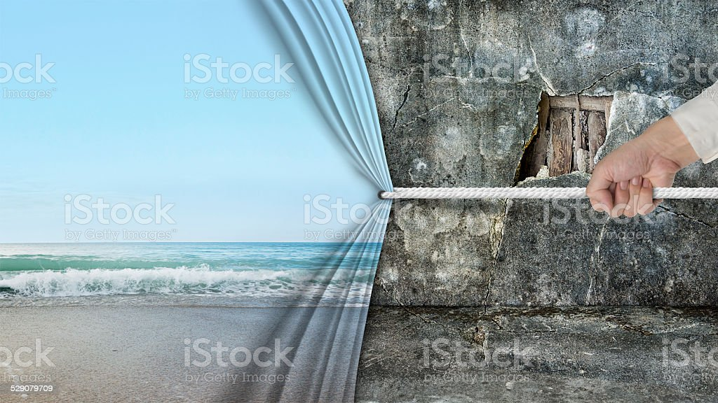 hand pulling natural sandy beach curtain covered old broken wall stock photo