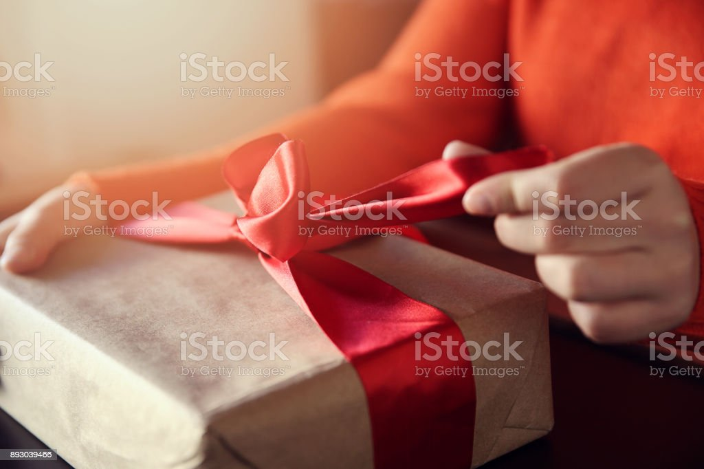 Hand pulls red ribbon on a gift wrapped in brown paper stock photo