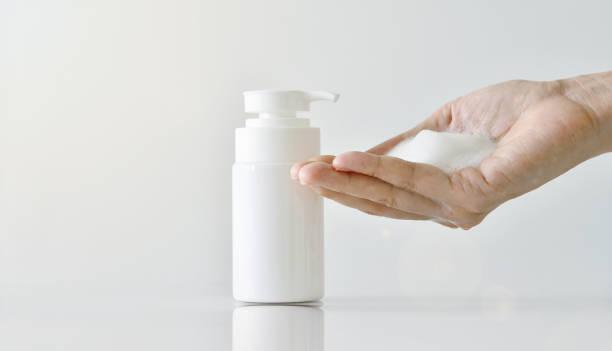 mão de bombeamento espuma de limpeza, limpador da cara, recipiente de bomba de espuma de cosméticos. - squeeze bottle - fotografias e filmes do acervo