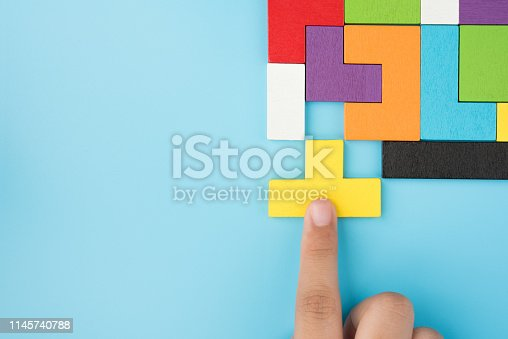 Hand push last piece jigsawto finish success planning concept solve puzzle isolated on blue background top view , logical thinking