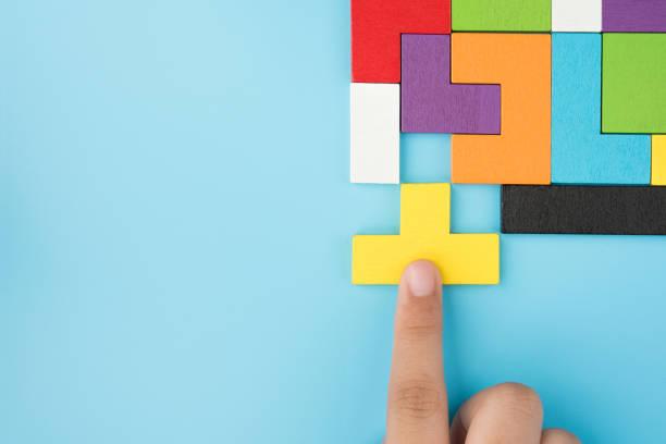 ハンドプッシュ最後のピース jigsawto 仕上げの成功計画コンセプトは、青の背景のトップビュー、論理的思考に孤立したパズルを解きます - 終わり ストックフォトと画像