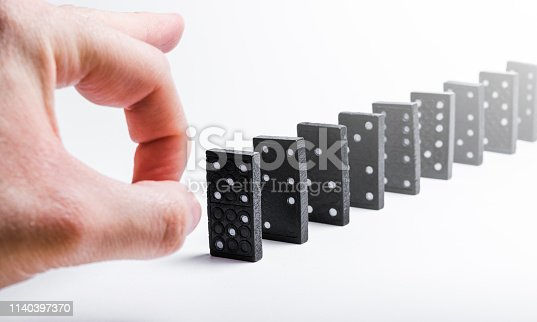 84743203 istock photo A hand pushes a group of black dominoes in a row that fall one after the other with a domino chain effect 1140397370