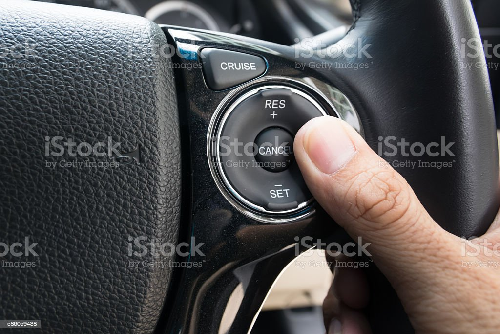 hand pushes Cruise control buttons stock photo