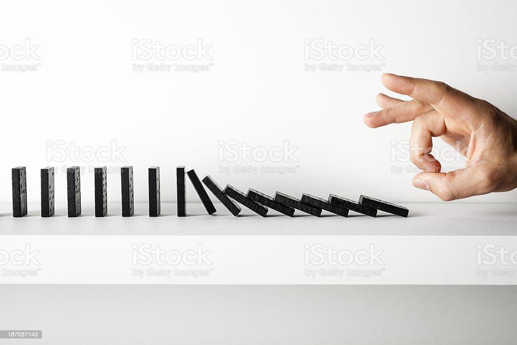 Hand pushing dominoes on shelf stock photo