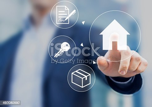 Hand pushing house button on screen with mortgage contract, keys and boxes