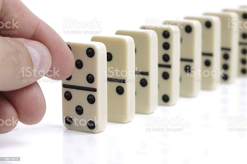 Hand pushing white dominoes royalty-free stock photo