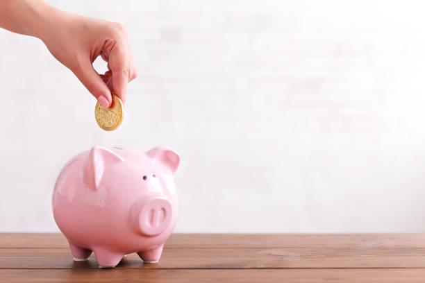 hand legen münze in rosa farbe sparschwein - plus stock-fotos und bilder