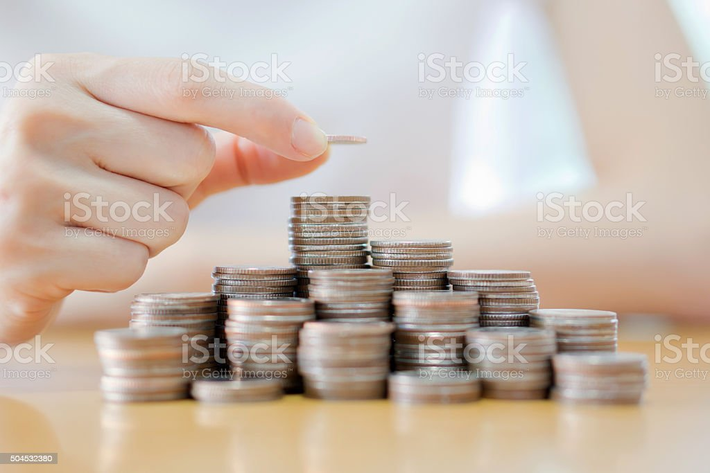 Hand put coins to stack of coins on white background stock photo