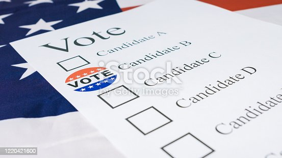 1001757106 istock photo Hand put I Voted Today sticker on ballot paper 1220421600
