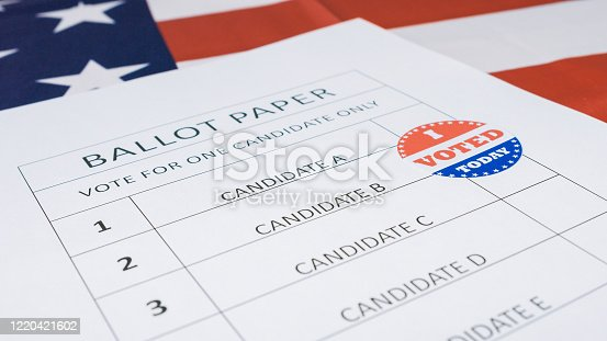 1001757106 istock photo Hand put I Voted Today sticker on ballot paper 1220421602