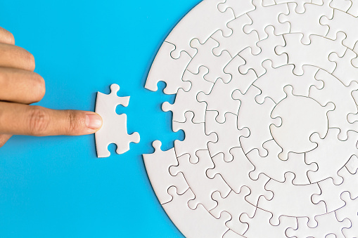 Hand put the last piece of jigsaw puzzle to complete the mission. Completing final task, missing jigsaw puzzle pieces and business concept with a puzzle piece missing.