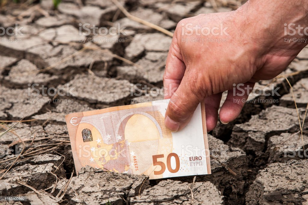 A hand puts a fifty euro note in the dried-up soil. - Royalty-free Accidents and Disasters Stock Photo
