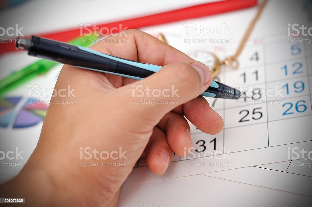 hand puts a mark on calendar stock photo