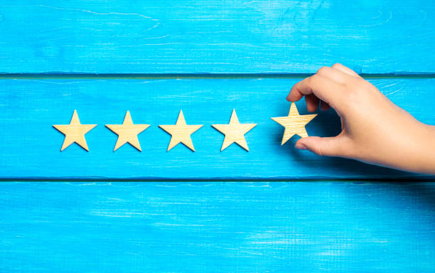 hand puts the fifth star. Quality status is five stars. A new star, achievement, universal recognition.The critic determines the rating of the restaurant, hotel, institution. Quality mark. stock photo