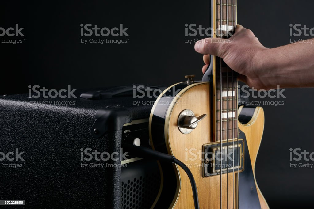 Hand puts vintage wooden electric bass guitar to combo amplifier stock photo