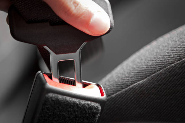 Hand putting a buckle into a car seat belt stock photo