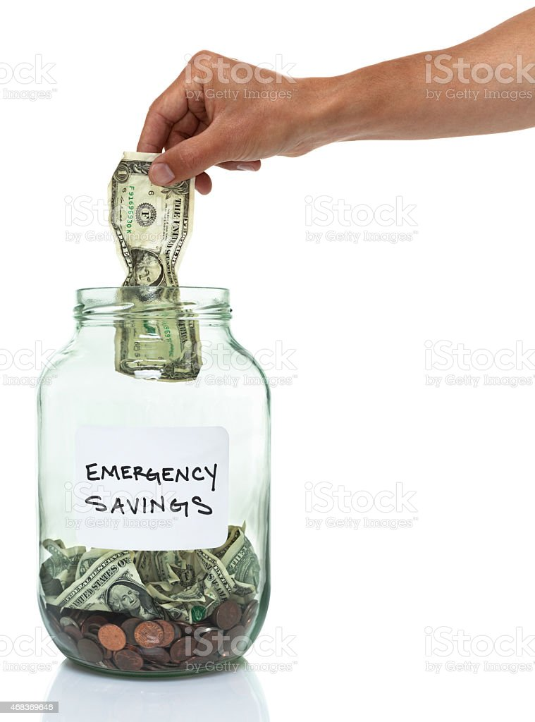 hand putting a dollar bill in an emergency savings jar stock photo