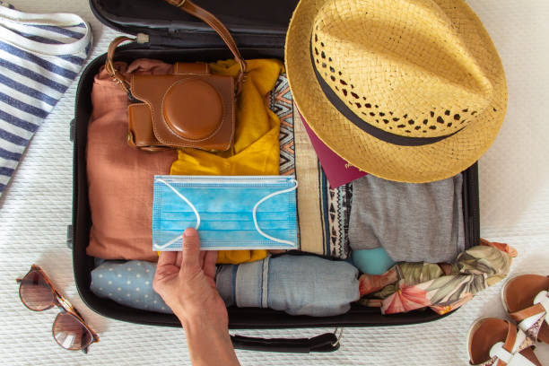 hand sätta en ansiktsmask på resväskan beredd att resa på sommaren, i det nya normala, efter coronavirus covid 19 pandemi. det finns andra tillbehör som en hatt, en kamera och en bikini. - resande bildbanksfoton och bilder