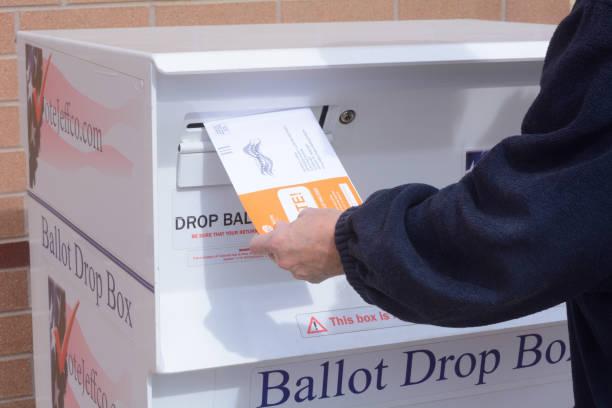 hand putting ballot envelope into jefferson county colorado ballot drop box - ballot stock pictures, royalty-free photos & images