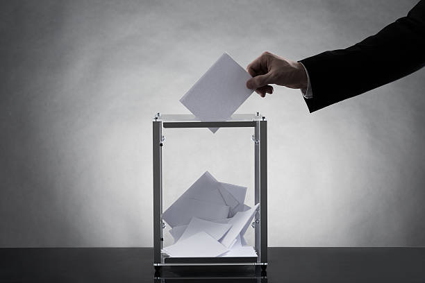 Hand Putting Ballot In Glass Box stock photo