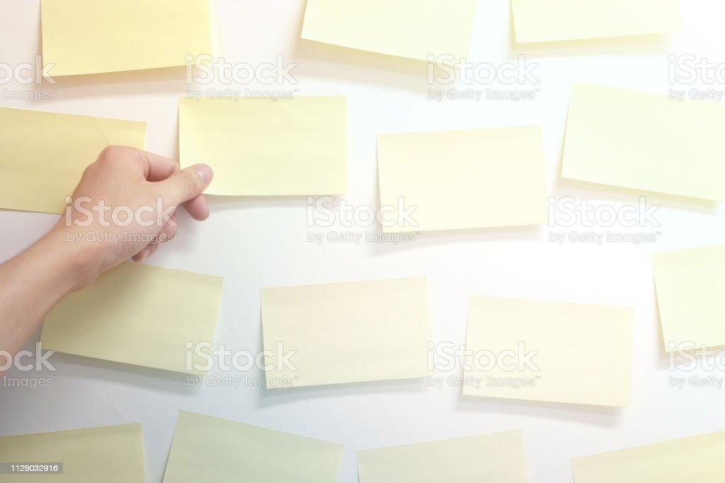 Hand, leere Haftnotizen auf Wand – Foto
