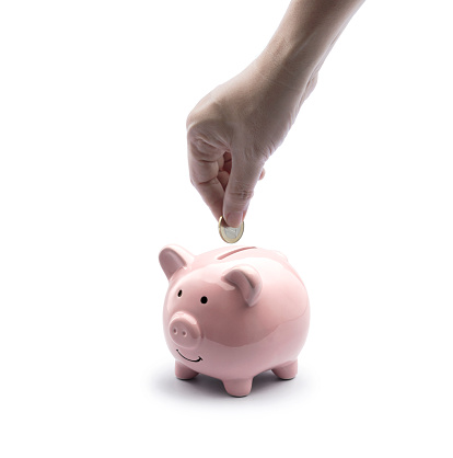 saving money on pink piggy bank isolate. hand putting coin into pig doll bank on white background