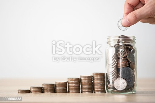 Hand putting coin to saving jar and coins stacking. Money saving investment profit and dividends concept.