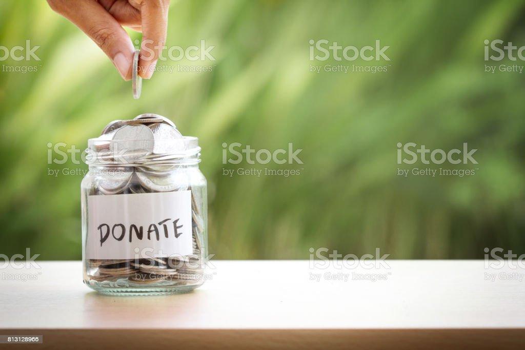Paralar vererek ve bağış konsepti için cam kavanoza koyarak el - Royalty-free ABD Stok görsel