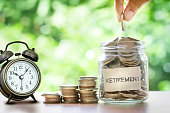 istock Hand putting Coins in glass jar with retro alarm clock 622064048