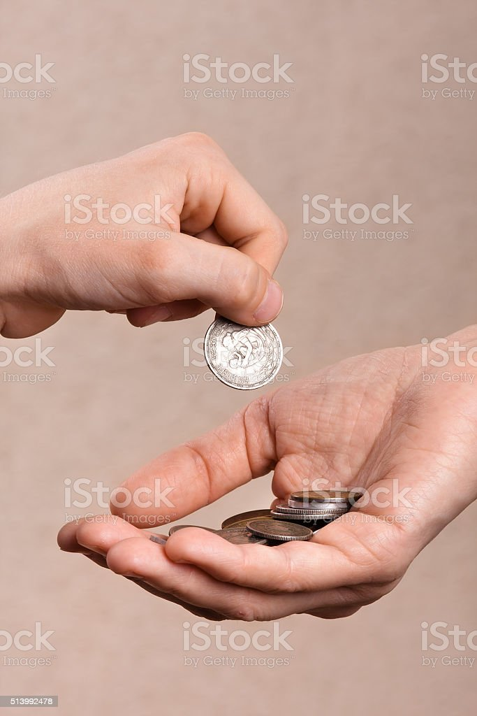 hand putting coins in the hand of another person stock photo