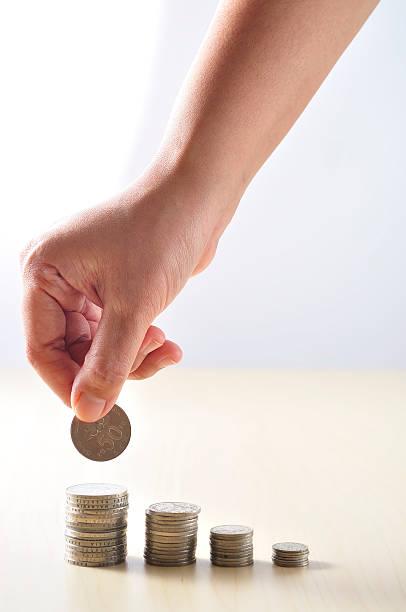 Hand setzen Münze auf Schreibtisch, Sparen-Konzept, Geringe Tiefenschärfe – Foto