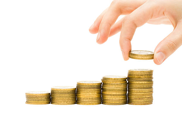 Hand putting coins on golden money stacks stock photo