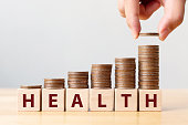 istock Hand putting coins on stack stair as step growing growth and wooden cube block with word HEALTH. Investment health and insurance fund concept 1157947296