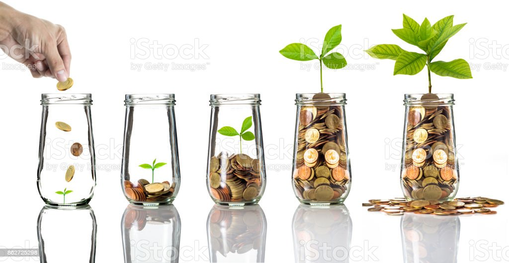 Hand putting gold coins into clear bottle on white background,Business investment growth concept stock photo