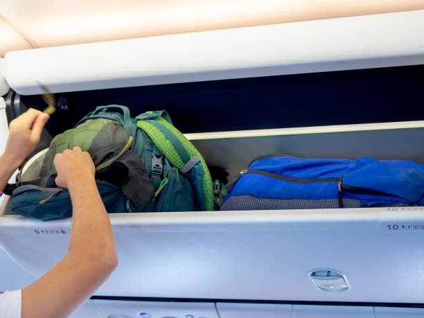hand putting green backpack on airplane locker - bin stock pictures, royalty-free photos & images