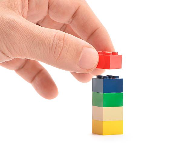 hand putting lego block - lego stockfoto's en -beelden