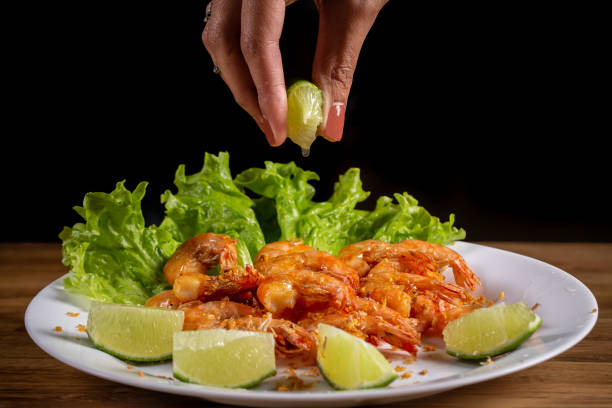 hand putting lemon on portion of shrimp fried in garlic and oil on wooden background. hand putting lemon on portion of shrimp fried in garlic and oil on wooden background. estudio stock pictures, royalty-free photos & images