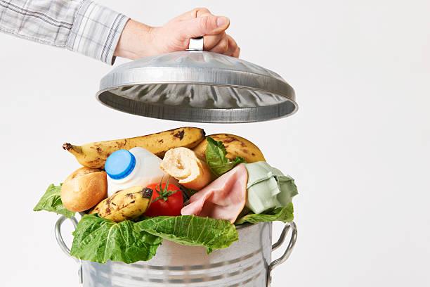 main mettre couvercle de poubelle pleine de déchets de nourriture - détritus photos et images de collection