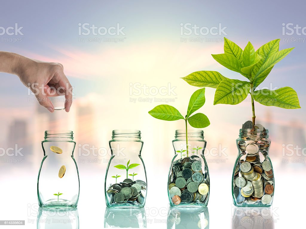 Hand putting mix coins and seed in clear bottle stock photo
