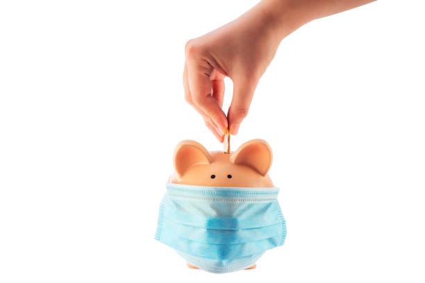 Hand steckt Geldmünze in Sparschwein mit Maske für die Ersparnis von Geld vermögen und Finanzkonzept – Foto