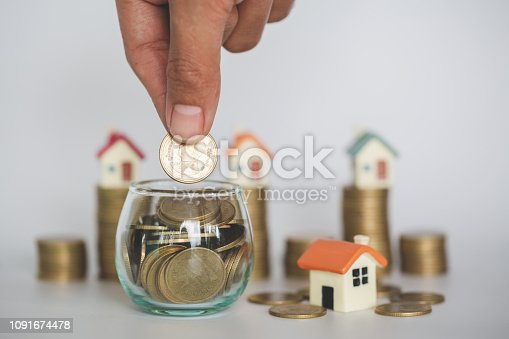 Hand putting money coin stack ,  buy a house,Risk,  Indicates the growth of home and finance, planning savings money of coins to buy a home concept property mortgage and investment for a house.