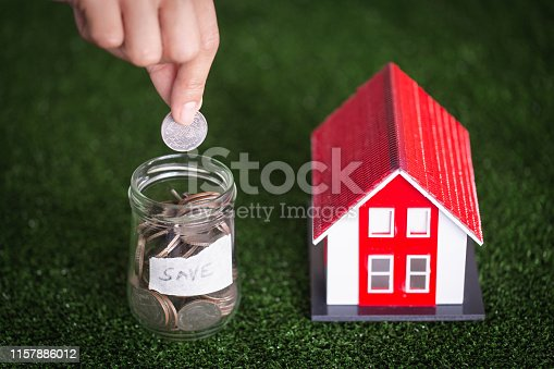 958039576istockphoto Hand putting money coin stack with model house; Property investment and house mortgage financial concept, 1157886012