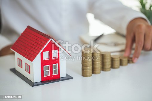958039576istockphoto Hand putting money coin stack with model house; Property investment and house mortgage financial concept, 1188905915