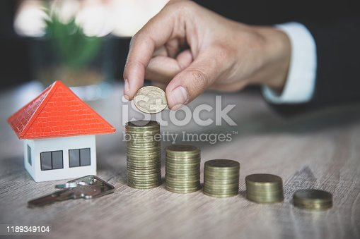 958039576istockphoto Hand putting money coin stack with model house; Property investment and house mortgage financial concept, 1189349104