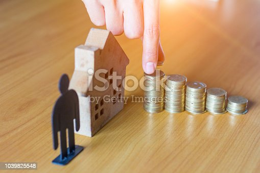 958039576istockphoto Hand putting money coin stack with wooden house; Property investment and house mortgage financial concept, 1039825548
