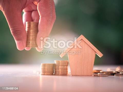 Hand putting money coins with home model on nature green background and sunlight. Finance and house loan, refinance, Property Investment and business, credit concept. with copy space