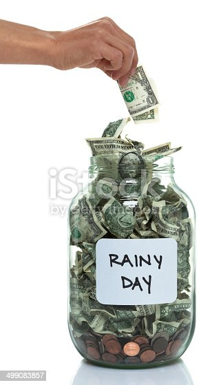 Hand putting money into a savings jar with a white rainy day label