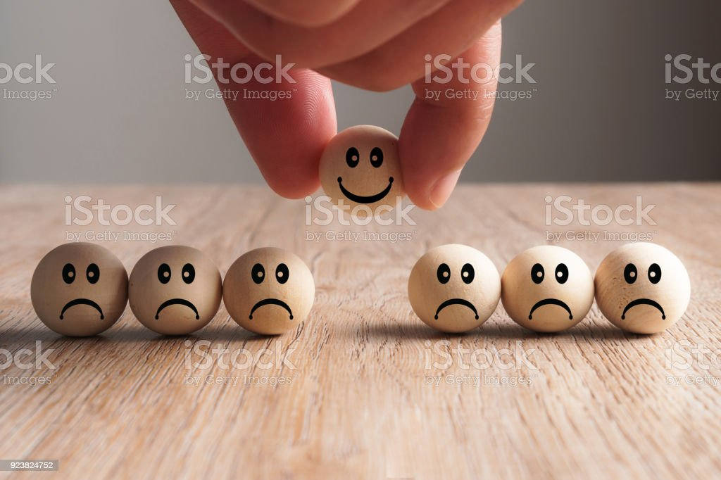 Hand putting on a smiling wooden ball, Concept of recruiting stock photo
