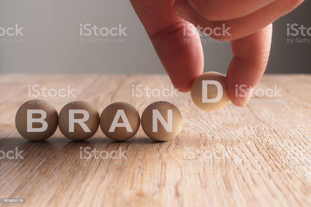 Hand putting on brand word written in wooden ball – zdjęcie