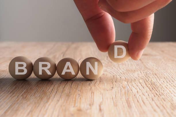 mão, colocando a palavra marca escrita em bola de madeira - soldado raso - fotografias e filmes do acervo
